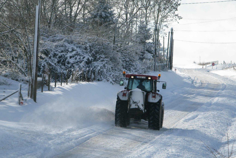 contrat de déneigement : le tracteur avec sa lame à neige et son bac à saler